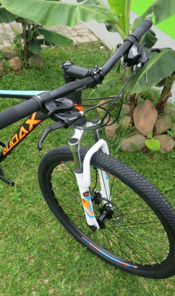 """A bike possui aros de 29"""", suspensão dianteira Zoom de 80mm, freio à disco mecânico, pneus Chaoyang e componentes Shimano."""