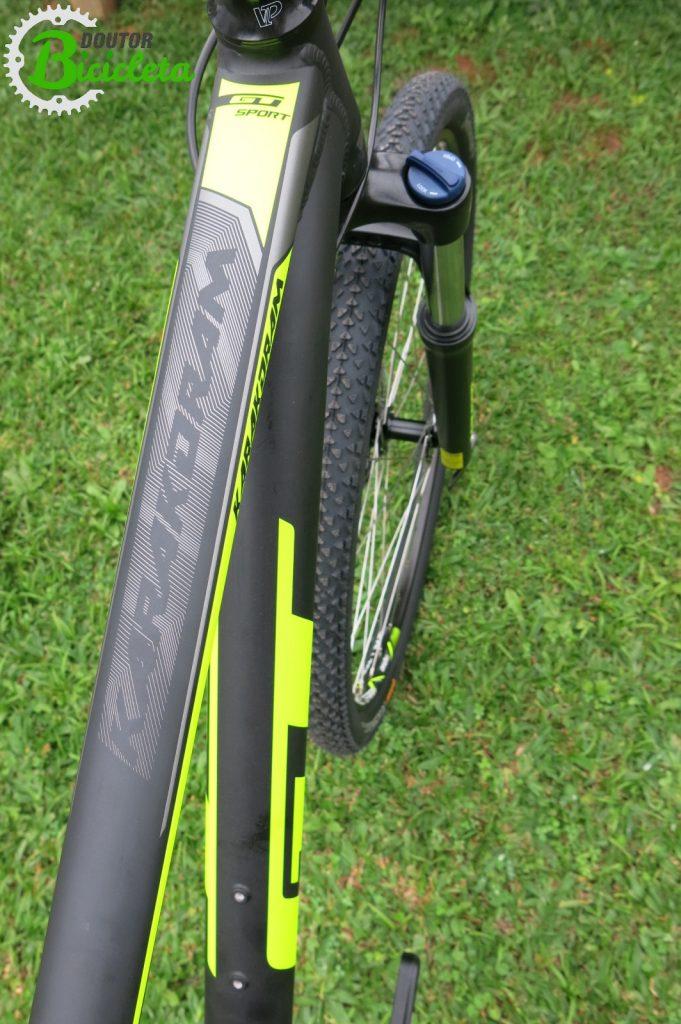 Detalhe das cores vibrantes da bicicleta; selim possui faixa com mesmo tom neon