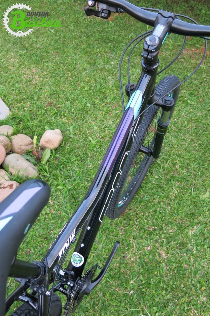 Detalhes nas cores da bicicleta no selim, avanço e parte frontal do guidão.