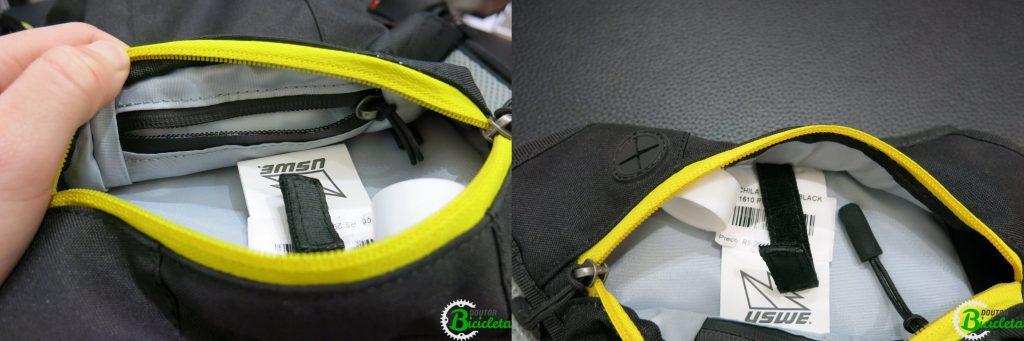 No lado esquerdo da imagem, bolso resistente à água com zíper. No lado direito, gancho de velcro e saída para cabos/fones de ouvido.