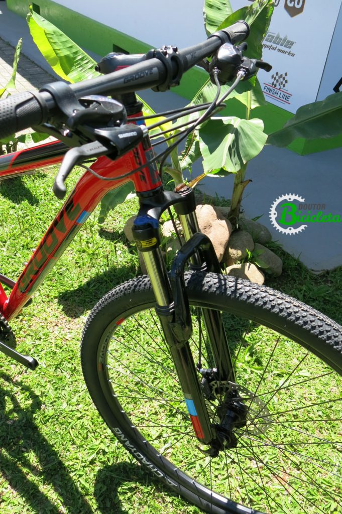 """A bike tem aros de 29"""", suspensão dianteira com trava, penus Chaoyang e freios à disco mecânicos."""