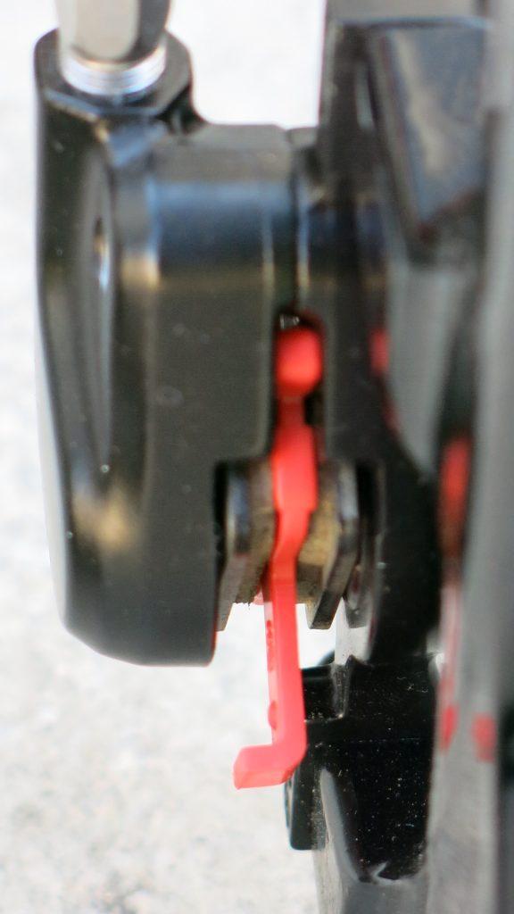 Detalhe: peça vermelha acompanha bicicletas com freio hidráulico e deve ser instalada entre as pastilhas quando a roda não está instalada.